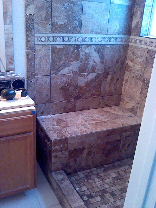 Tile work is completed with a leading bullnose edge and smaller tiles for the shower pan.