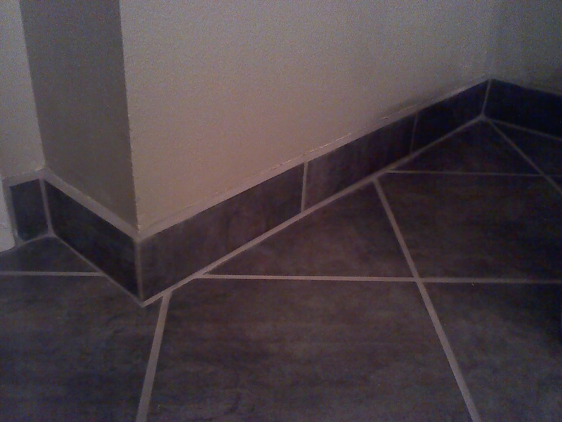 Tile base cove is installed with a 45 degree beveled grout edge.